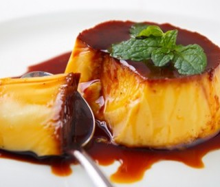 *** Local Caption *** Caramel custard pudding and spoon on plate with lemon balm leave on top
